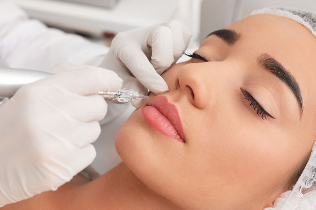 Young woman undergoing procedure of permanent lip makeup in tattoo salon, closeup.jpg