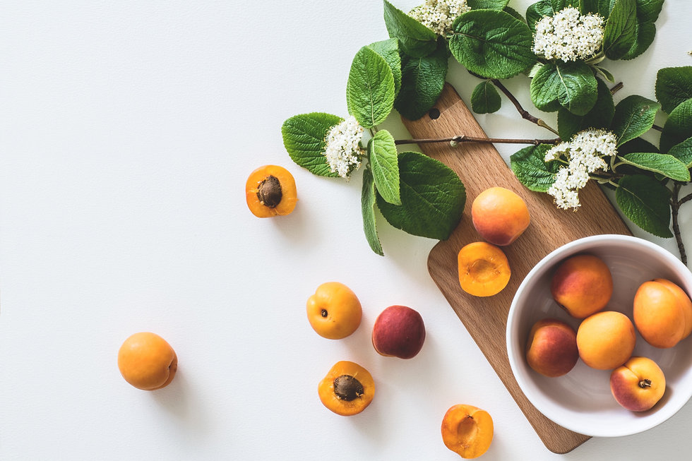 a bowl of peaches and basil sitting on a wooden cutting board