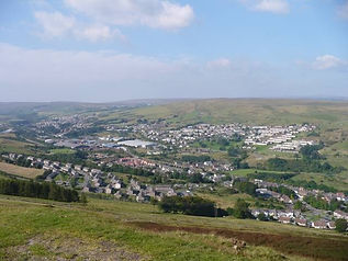 A huge landscape shot of Pontlottyn and the surrounding area showing houses, mountains, factories and trees.