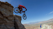 A free riding mountain biker jumping off a high rock face in the desert opposite the Suspension Inc booking link