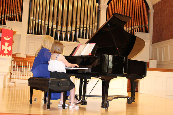 Lana teaching a student to play the Grand Piano in Delray Beach. Lana giving music lessons in Delray Beach and Boca Raton.