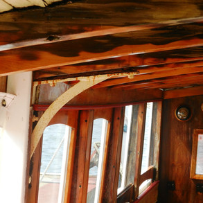 Old deckhead showing corroded bracket and rot in deck beams (Dark Areas)