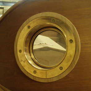 Close up of midships porthole showing the compound shape of the timber backing piece.
