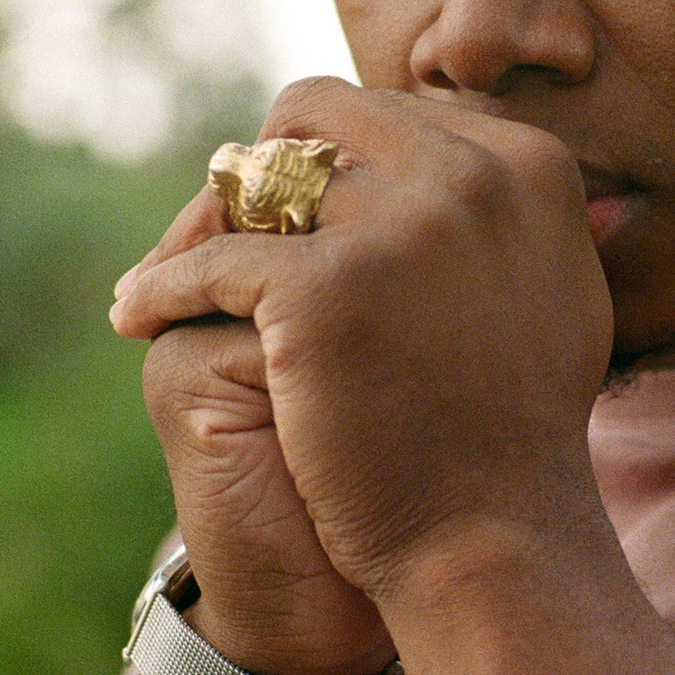 Black man's hands with a gold lion ring