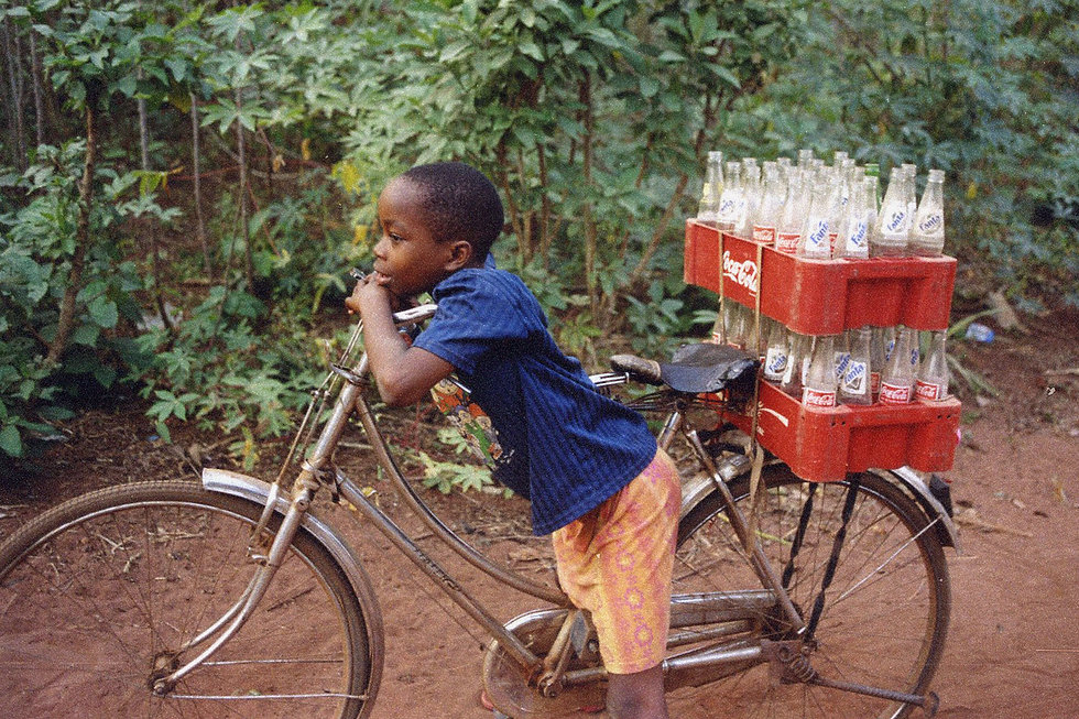 Nigerian kid resting on bicycle with Coca Cola bottles mounted on the bicycle