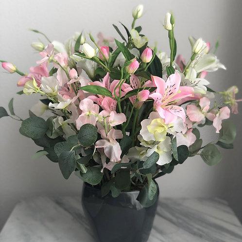 Künstliches Arrangement mit Lilien in einer Vase
