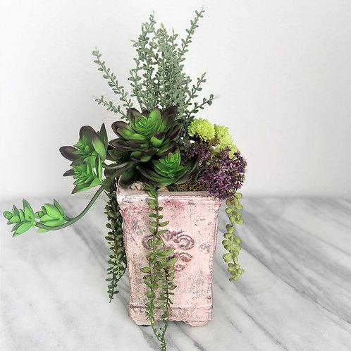 Künstliche Sukulenten in einer Vase aus Beton