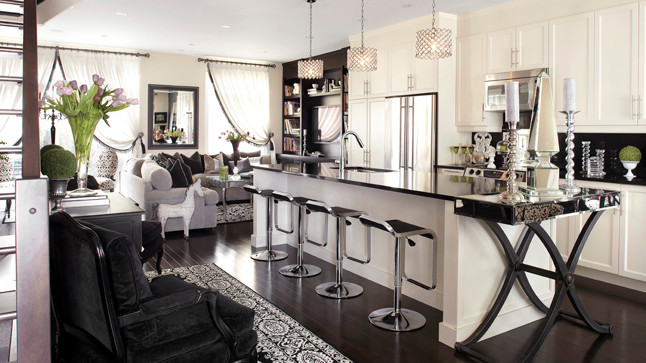 Extending the counter of the island, a mirrored glass and cross leg console turns into a space to serve meals.