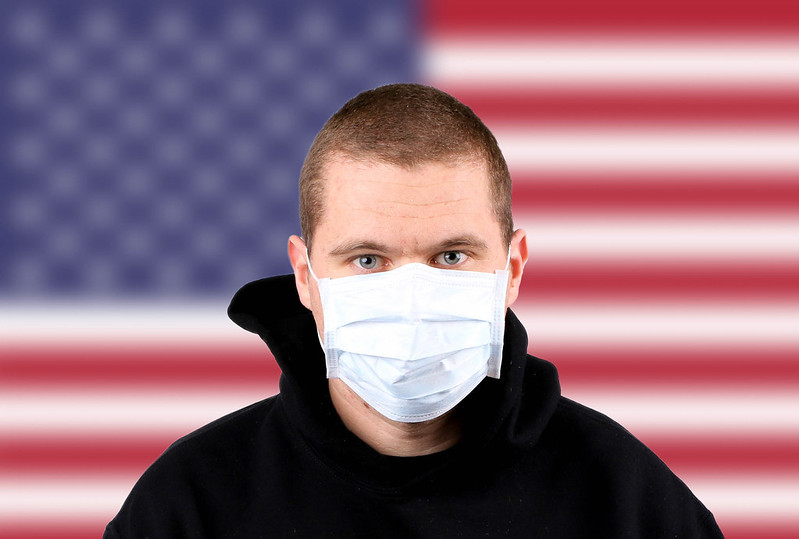 Photo: Man wearing protection face mask with flag of USA by Marco Verch under Creative Commons 2.0
