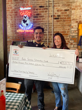 Chef Aarón Sánchez accepting a donation from Gus's Fried Chicken