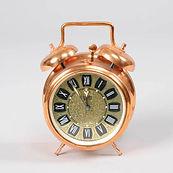 Réveil de forme cylindrique de couleur cuivrée. Une poignée et deux cloches sont sur le dessus du réveil. Deux pieds le maintiennent debout. Un seul cadran pour les heures et pour le réveil. Chiffres romains.
