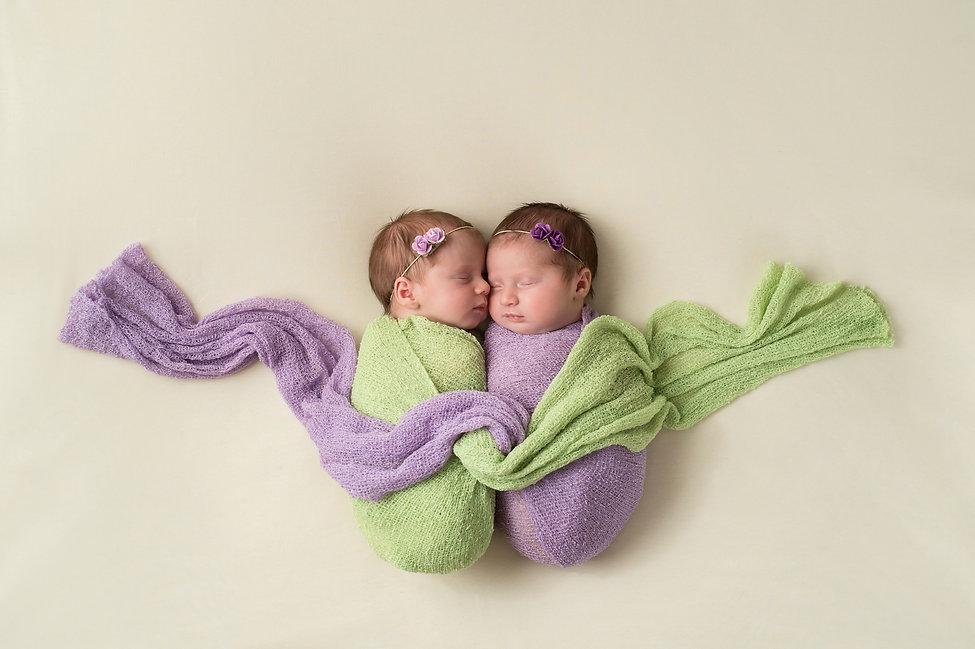 Fraternal twin newborn baby girls swaddl