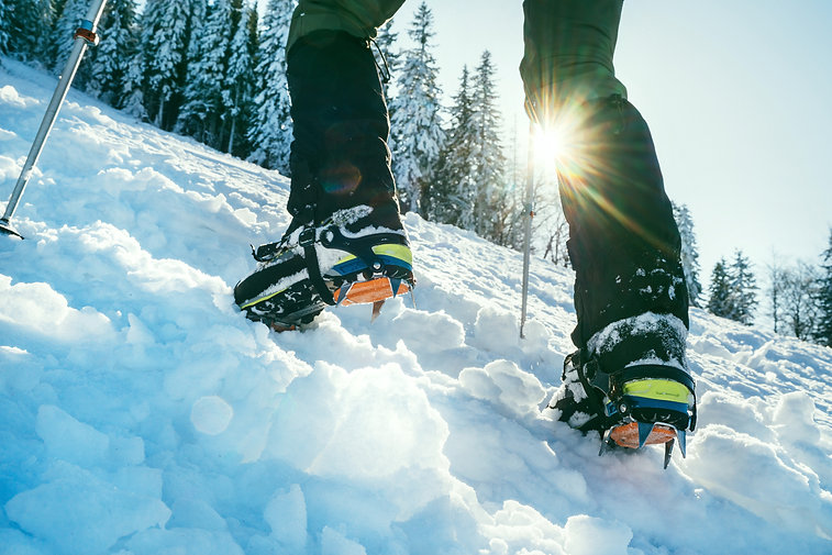 Close up shot of mountain boots with crampons and snow gaiters with backlight sun beams an