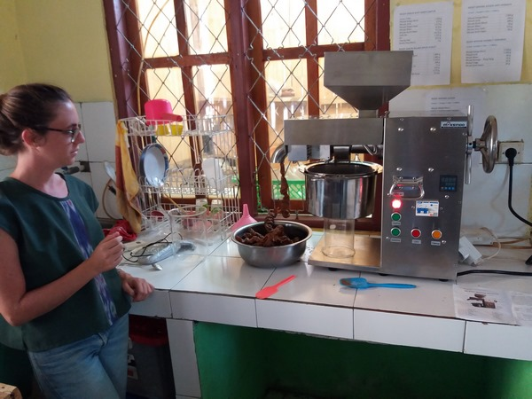 Marie LAFFON, volontaire appui développement économique, en plein test de pressage d'huile végétale