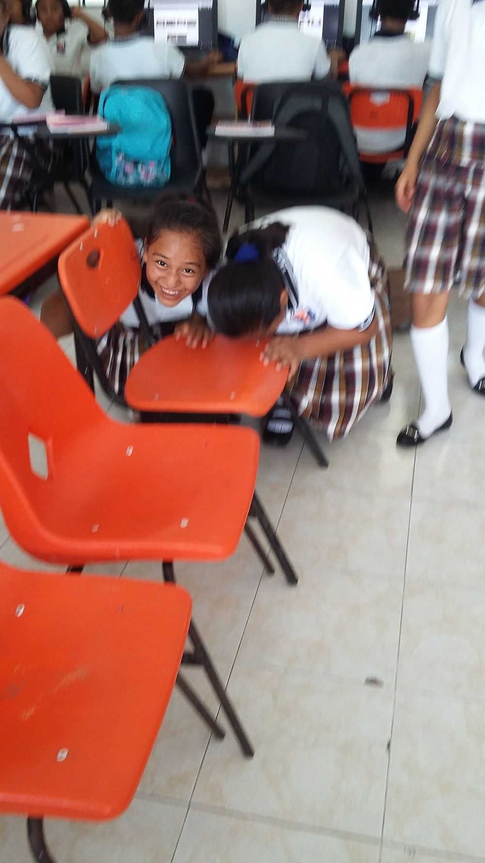 Michelle and Ximena ,grade 7 students love to participate.They are putting their nose on the chair.