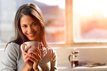 Woman drinking coffee at home with sunri