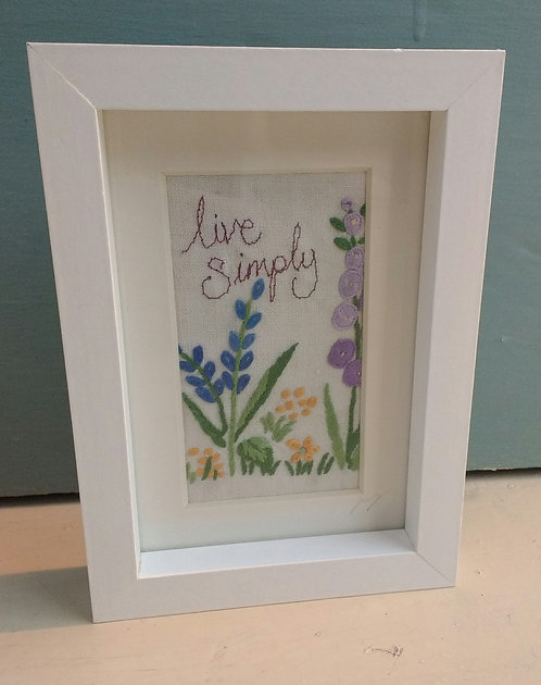 Embroidered 'live simply' frame