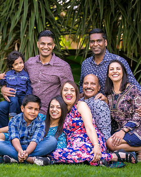 Indian family photo of 8 members sitting on the lawn and smiling