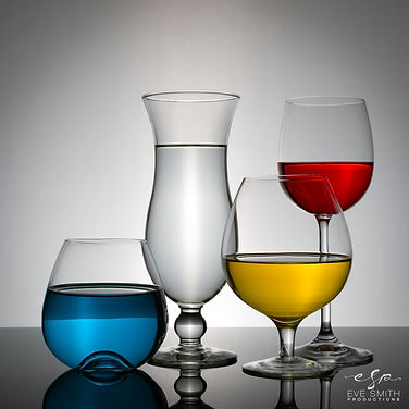 4 clear glasses filled with red, blue, clear and yellow liquid. Glasses on black perpex against a white backdrop. Photo taken from the front.