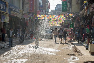 Throwing water to settle dust in the streets of Kathmandu, Nepal