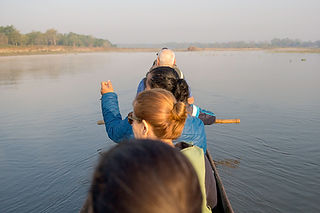 People on a log boat on Rapti River, Chitwan National Park, Nepal
