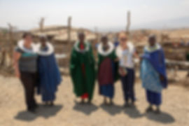 Shots and Tales | Corinne Fenech and Dorianne Mallia posing with Maasai women | Oldupai Gorge Tanzania