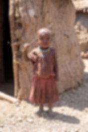Shots and Tales   Maasai child near a mud hut in a boma   Oldupai Gorge Tanzania