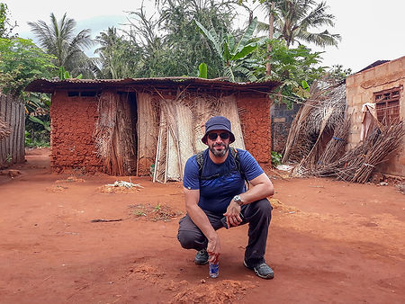 Traditional mud hut and tourist at the village of Kigunda, red earth village tour, Zanzibar, Tanzania | Shots and Tales