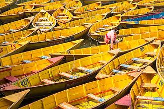 Yellow boats and a Nepal woman on Bengas Lake in Pokhara, Nepal