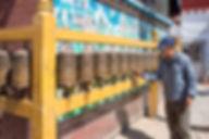Man turning Buddhist Prayer Wheels at Boudhanath, Boudha Stupa, Kathmandu, Nepal