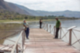 Three people on a pier at Lake Manyara, Tanzania, Shots and Tales Crew