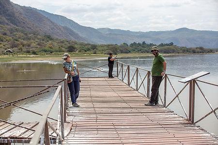 Three people on a pier at Lake Manyara, Tanzania, Shots and Tales Crew