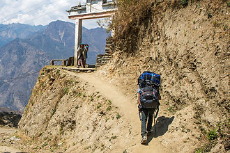 Porter arriving at Paudwar Village, Annapurna-Dhaulagiri Community Trail, Nepal