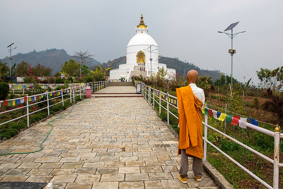 White Buddhist stupa and monk in orange at World Peace Pagoda (Shanti Stupa), Pokhara, Nepal