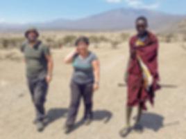Shots and Tales | Corinne Fenech and Noel Fenech walking with Maasai man in a boma | Oldupai Gorge Tanzania