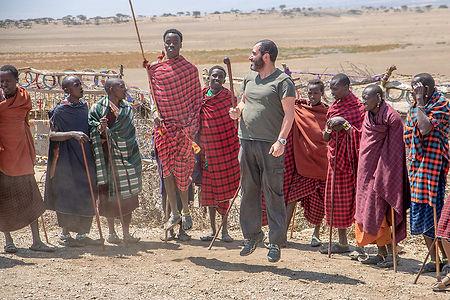 Shots and Tales | Noel Fenech jumping (not very high) with Maasai men at a boma | Oldupai Gorge Tanzania