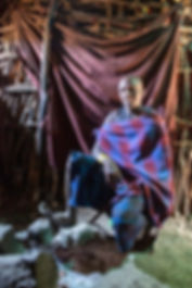Shots and Tales | Maasai man wearing motorcycle tyre shoes in a Maasai mud hut in a traditional village | Oldupai Gorge Tanzania