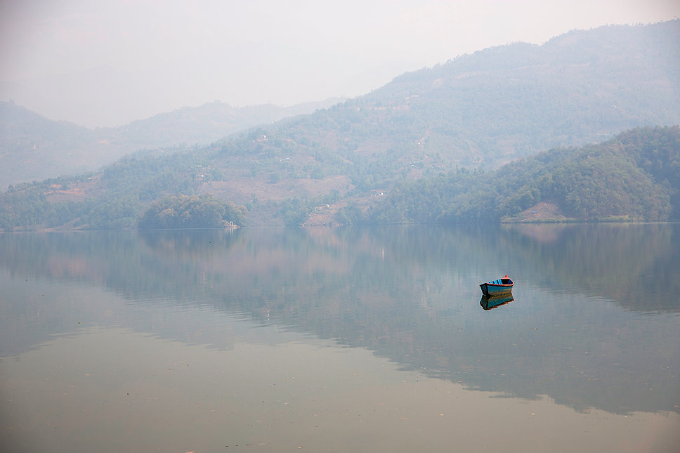 Blue boat in the middle of Bengas Lake, Pokhara, Nepal