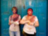 Two people with colourful faces on blue background during Holi – festival of colours in Kathmandu, Nepal
