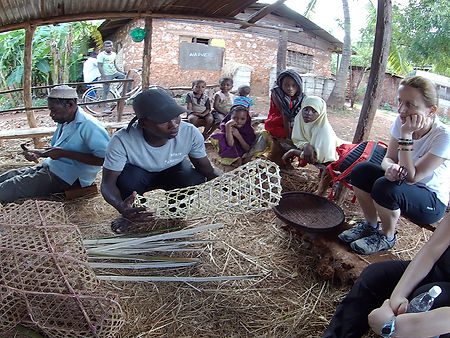 Tourists with fish net weavers explaining the trade in Kigunda village, Red Earth bicycle tour, Zanzibar, Tanzania, Shots and Tales