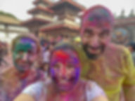 Three people with colourful faces during Holi – festival of colours in Kathmandu, Nepal
