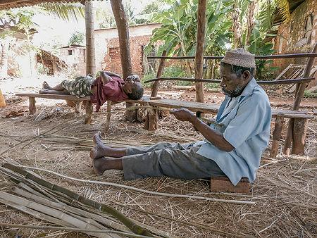 Two men, fish net weavers in Kigunda the Red Earth Village in Zanzibar, Tanzania | Shots and Tales