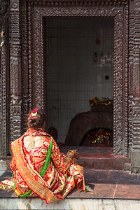 Woman in red and gold sari, praying at Tal Barahi Temple, Pokhara Nepa
