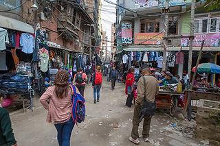 Unmade streets, shops and people walking in Kathmandu, Nepal