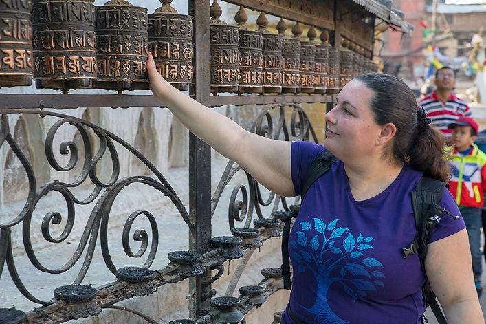 Woman turning Buddhist Prayer Wheels at , Swayambhunath Temple, Kathmandu, Nepal