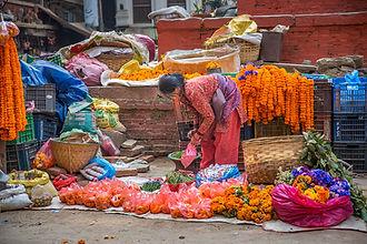 Woman selling marigold garlands and flowers in Kathmandu, Nepal