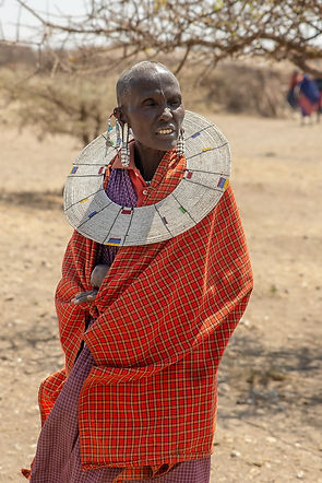 Shots and Tales | Maasai woman wearing red traditional clothes and jewellery at a Maasai Village | Oldupai Gorge Tanzania