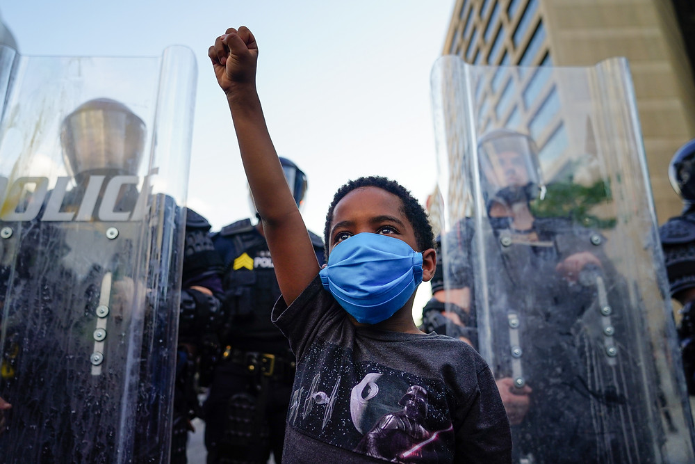 ATLANTA, GA - MAY 31: A young boy raises his fist for a photo by a family friend during a demonstration on May 31, 2020 in Atlanta, Georgia. Across the country, protests have erupted following the recent death of George Floyd while in police custody in Minneapolis, Minnesota. (Photo by Elijah Nouvelage/Getty Images)