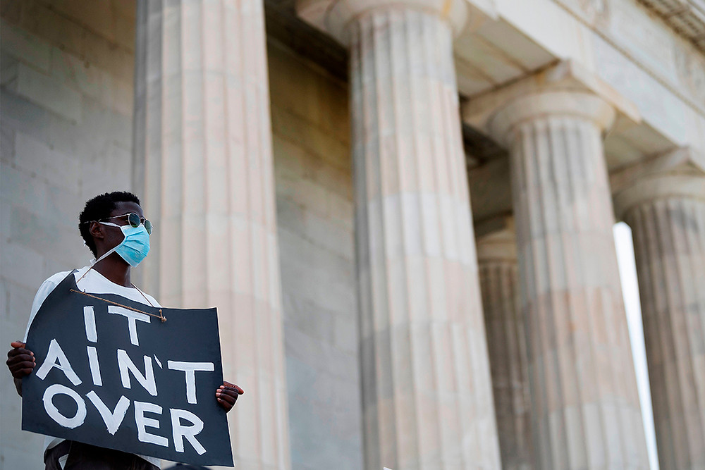 """Protestor Holds Sign """"It Ain't Over"""""""