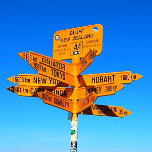 A sign post in Bluff, New Zealand pointing to different areas around the world such as Tokyo, New York and Sydney. The backdrop is an amzing New Zealand blue sky.
